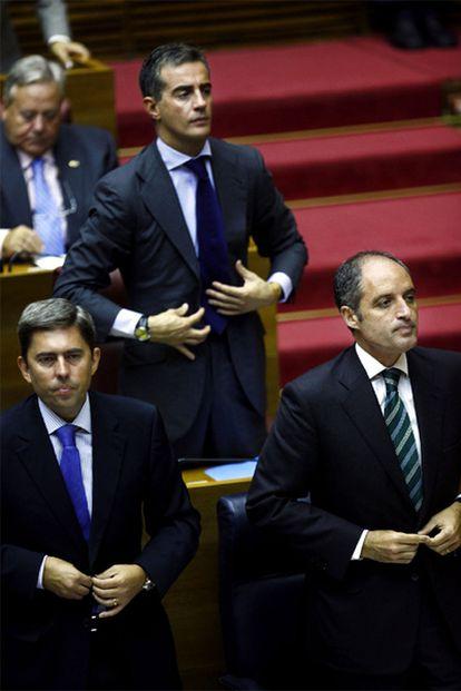 El presidente de la Generalitat Valenciana, Francisco Camps, (a la derecha), el vicepresidente, Vicente Rambla, (izquierda) y el portavoz del grupo popular en las Cortes, Ricardo Costa, se levantan al inicio del pleno de sesión de control en las Cortes Valencianas el 30 de septiembre de 2009.