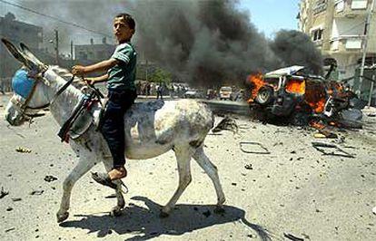 Un niño palestino pasa montado en un burro ante el coche del líder de Hamás, Abdelaziz Rantisi, tras el ataque israelí en Gaza, ayer.