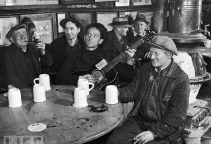 Woody Guthrie actuando en una taberna de Nueva York en 1943 con su famosa guitarra con el lema impreso 'Esta máquina mata fascistas'.