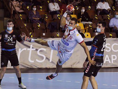 Donlin, del Ademar León, lanza entre dos jugadores del Sinfín, en el partido del 10 de octubre.