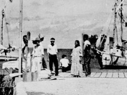En el centro del grupo del malecón está la figura que History Channel apunta que pudo ser Amelia Earhart. A a izquierda, junto al poste, el supuesto Noonan.