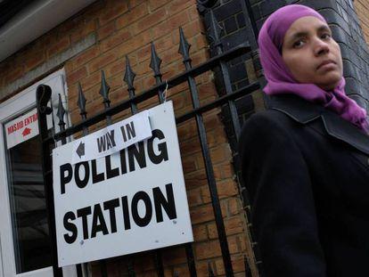 Una mujer sale de un colegio electoral. En vídeo, las reacciones de los líderes políticos tras conocer el avance de resultados de las elecciones generales.