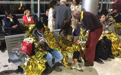 Grupos de pasajeros arropados con mantas térmicas en la estación de Calais (Francia), el 2 de septiembre de 2015.