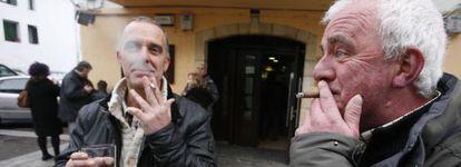 Dos hombres fuman y beben en la calle, frente a un bar en la calle de San Pedro de Hondarribia (Fuenterrabia, Guipúzcoa)