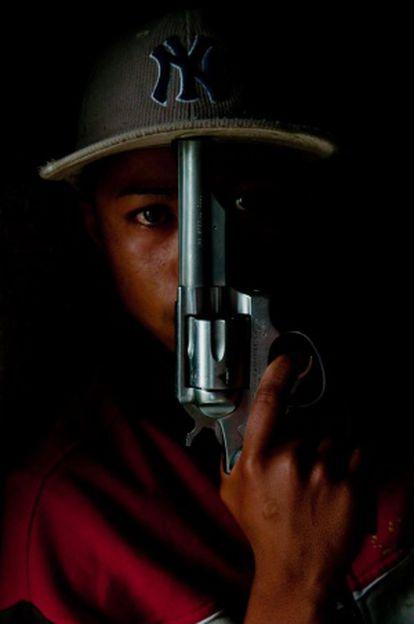 Un sicario posa con un revólver.