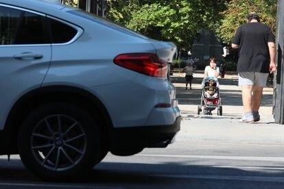 Una mujer pasa ante un SUV con su carrito de bebé, en Madrid.