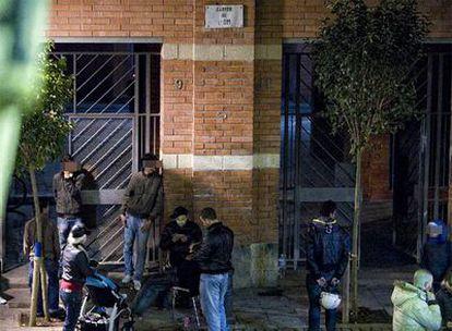 Viandantes y jóvenes charlan frente a la entrada del edificio donde está el piso <i>ocupado</i>.