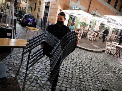 Un camarero recoge las sillas, el viernes, en un restaurante del Trastévere (Roma).