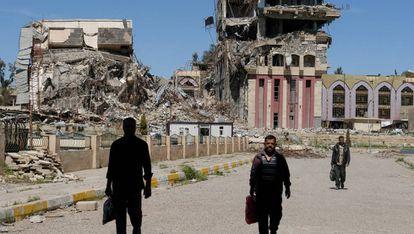 Unos ciudadanos caminan por los alrededores de lo que queda de la Universidad de Mosul.