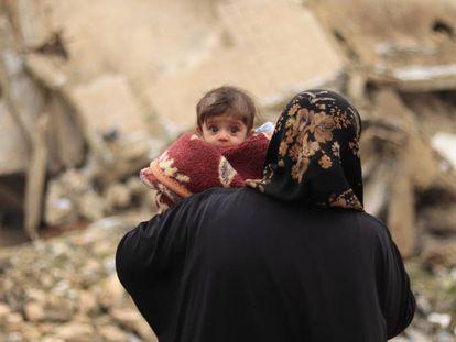 Una madre pasea con su bebé en brazos por las calles de Alepo el pasado mes de enero.