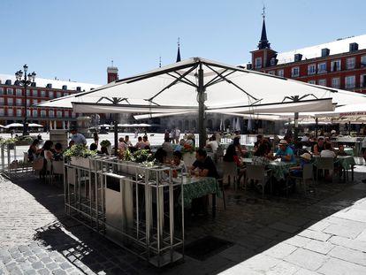 Varios turistas en la terraza de un restaurante de la plaza Mayor de Madrid, este sábado.