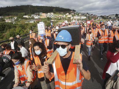 Dos hombres portan una simulación de un féretro en una manifestación, este domingo, por el futuro de  las fábricas de Alcoa y Vestas, en A Mariña (Lugo).