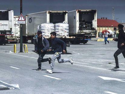 Jóvenes marroquíes corren ante la presencia de la Guardia Civil en el puerto de Ceuta.