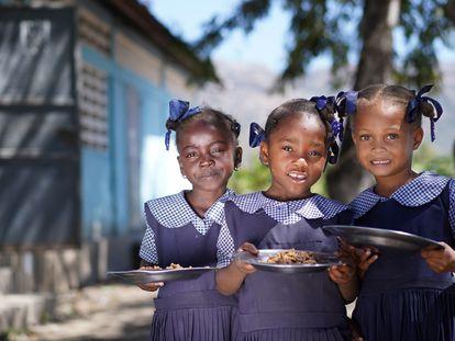 Tres niñas haitianas posan con sus platos de bulgur en su escuela. El Programa Mundial de Alimentos sirve hasta 250.000 menús a diario en las escuelas del país. FOTO: ANTOINE VALLAS/VIDEO: ALEXIS MASCIARELLI (WFP)