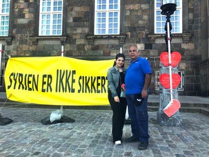 """Mohamed Alderi y su hija Sara, refugiados sirios en Dinamarca, el jueves frente al Parlamento. En el cartel se lee en danés """"Siria no es segura"""". / C. G."""