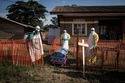 Trabajadores sanitarios desinfectan un ataúd durante un entierro seguro en agosto de 2018 en Beni, noreste del Congo.