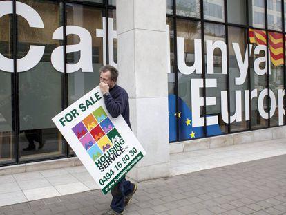Un hombre con un cartel de se vende pasa por delante de la fachada de la sede de la Embajada de la Generalitat de Cataluña en Bruselas (Bélgica).