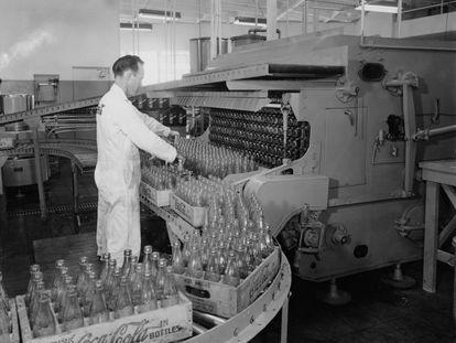 Un trabajador embotella Coca-Cola en una imagen de 1955.