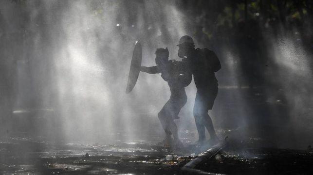 Manifestantes se escudan del rocío de un cañón de agua de la policía que intenta dispersarlos en Santiago, Chile.