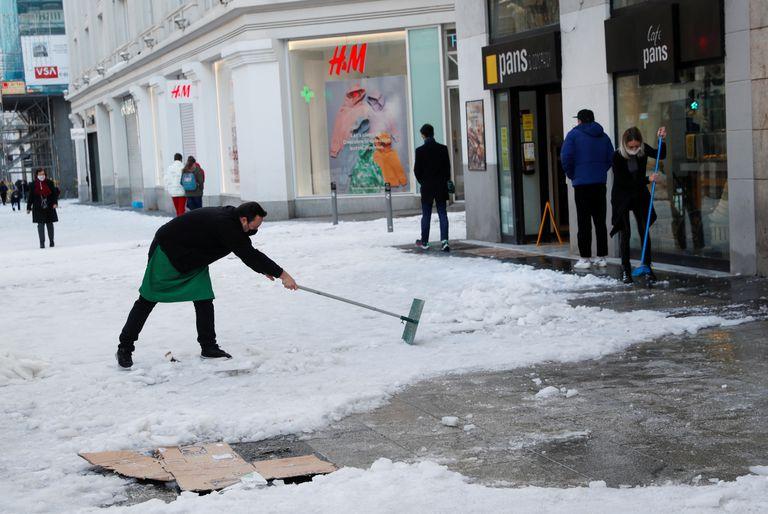 Varias personas retiran este lunes el hielo en la Gran Vía de Madrid.