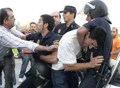 Policías antidisturbios reducen a miembros de un piquete frente a las instalaciones del puerto de Motril que querían evitar el paso de camiones con carburante.