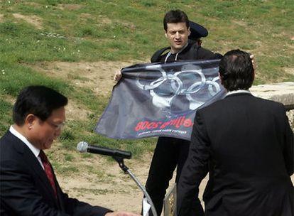 El activista de Reporteros sin Fronteras forcejea con los agentes mientras Lui Qi sigue con su discurso.