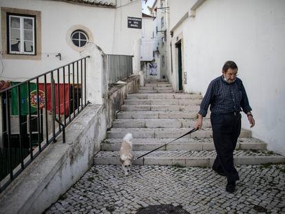 Un vecino pasea por la Alfama, el barrio más antiguo de Lisboa y con mayor número de pisos turísticos.