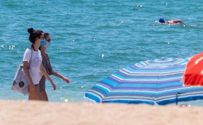 Dos jóvenes pasean con la mascarilla puesta por la orilla de la playa de La Antilla (Huelva).