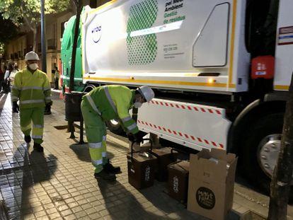 Trabajadores municipales hacen la recogida de la basura puerta a puerta en Sant Andreu.