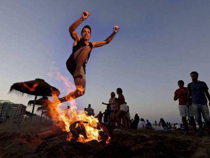 Un joven salta una hoguera en la playa de la Malvarrosa de Valencia, en una celebración de la noche de San Juan del pasado año.