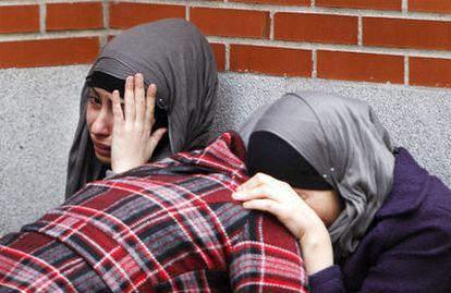 Tres mujeres lloran a las puertas de la casa donde ha sido asesinada la mujer.
