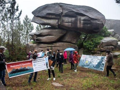 """Activistas protestan en la piedra de """"A Cascuda"""", en el monte de Pasarela, contra la instalación de parques eólicos cerca de esta zona de especial conservación en Vimianzo (A Coruña), el pasado 20 de mayo."""