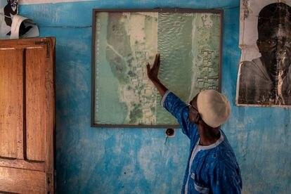En un mapa que tiene en su casa, Ahmet Sène Diagne enseña cómo era desde arriba Doun Bada Dièye, antes de que el pueblo quedase sumergido por completo en 2012.