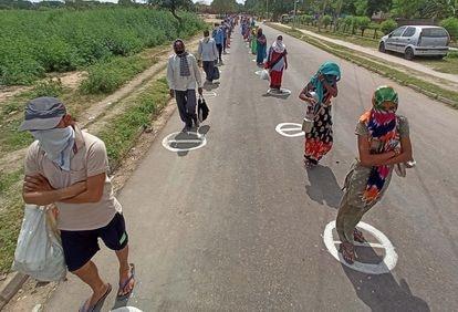 Vecinos de Kajheri Village, India, mantienen la distancia social mientras esperan a que repartan comida.