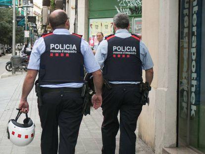 Una pareja de agentes de los Mossos d' Esquadra camina por el barrio de Sants.