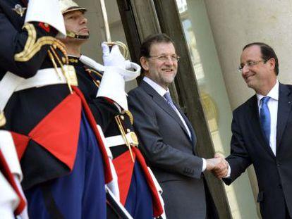 El presidente del Gobierno, Mariano Rajoy, saluda a François Hollande, en la puerta del Elíseo.