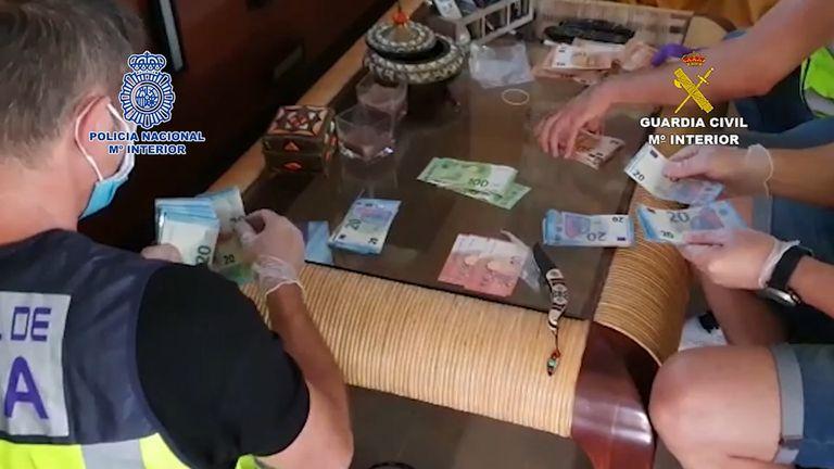 Varios policías cuentan el dinero incautado en uno de los registros de la operación Gilusu-Bones.