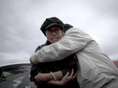 Liu Xia (izquierda) abrazada por un amigo fuera del centro de detención de Huairou.
