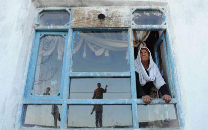 La viuda afgana Bibikoh se asoma a la ventana de su casa en Zanabad.