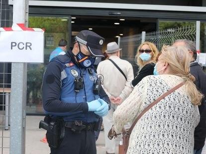 Un policía municipal pide este martes la documentación a una mujer antes de entrar al Centro Cultural Lope de Vega, en Puente de Vallecas, uno de los barrios confinados en Madrid.