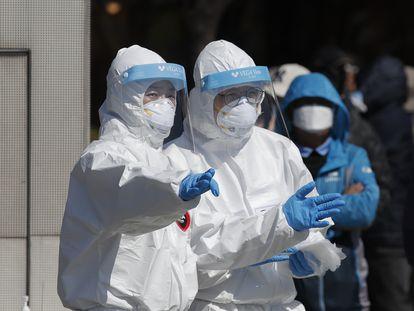 Personal sanitario con trajes de protección supervisa una prueba masiva en Seúl el pasado 22 de marzo.