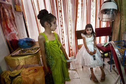 Dos chicas en un salón de belleza, vestidas y maquilladas para la boda de un familiar en Kabul, 2009.
