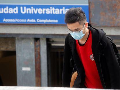 Un joven con mascarilla en el acceso a la estación de metro de Ciudad Universitaria, en Madrid.