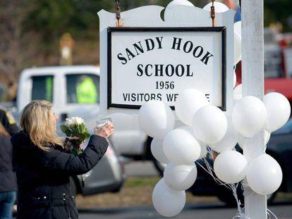 Andrea Jaeger lleva flores y una vela en el exterior de la escuela Sandy Hook, en Newtown.