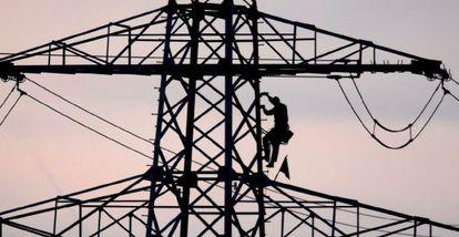Un operario repara una torreta eléctrica.