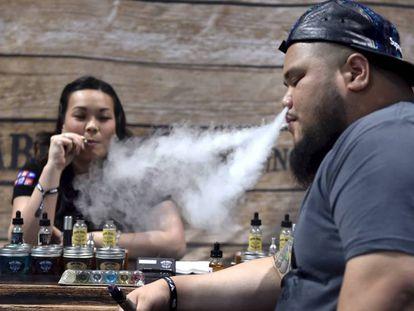 Dos personas fuman con cigarrillos electrónicos en un encuentro para vapeadores en Las Vegas. En vídeo, declaraciones de Barbara Ferrer, doctora del departamento de salud pública de LA.
