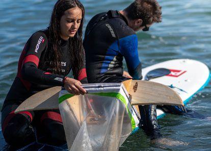 Voluntarios recogen plásticos en la playa de Barcelona para el proyecto Surfing for Science.