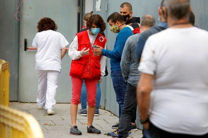Varias personas esperan su turno para realizarse una PCR durante el cribado masivo en Manlleu (Barcelona).
