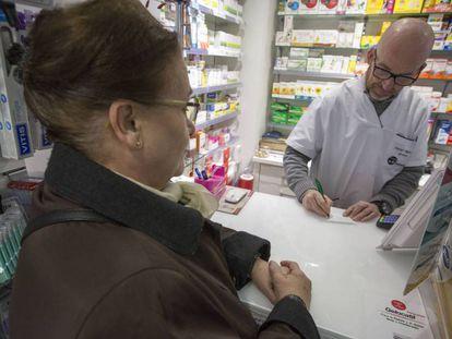 Una mujer compra un medicamento en una farmacia en Madrid.