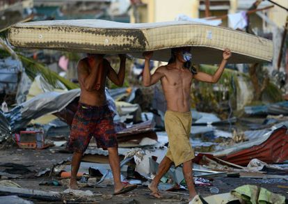 Dos hombres transportan sendos colchones en la provincia de Leyte.
